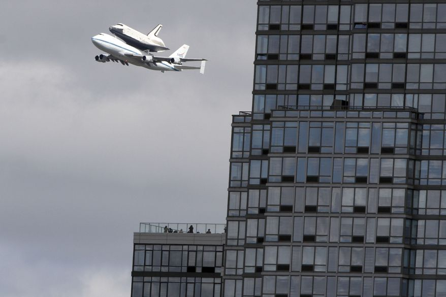 People watch from the balcony of a building as the space shuttle Enterprise, riding on the back of the NASA 747 Shuttle Carrier Aircraft, cruises over the Hudson river, Friday, April 27, 2012, in New York. Enterprise is eventually going to make its new home in New York City at the Intrepid Sea, Air and Space Museum. (AP Photo/Mary Altaffer)