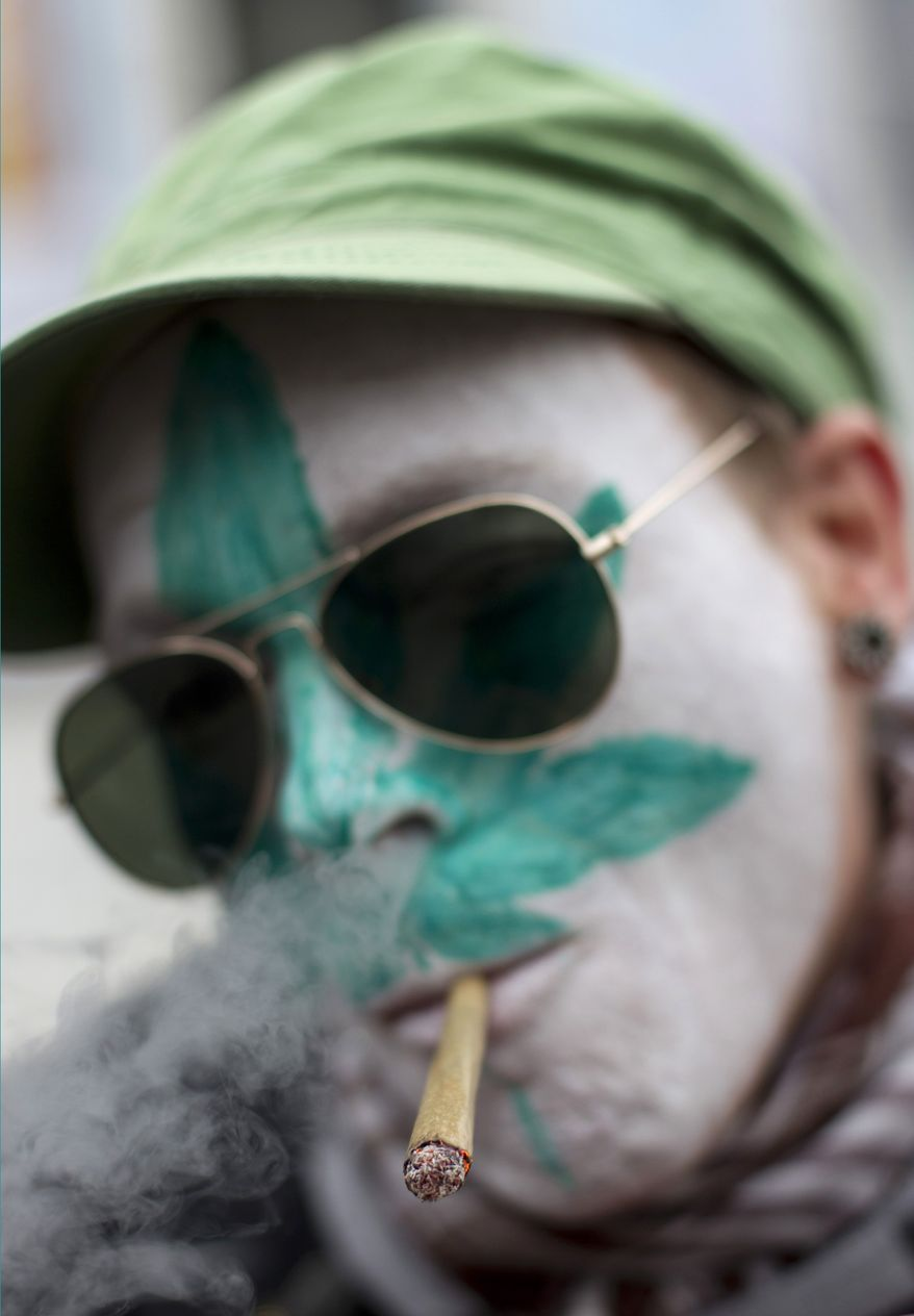 A protestor from Belgium with a marijuana leaf painted on his face smokes a marijuana joint in Amsterdam Friday, April 20, 2012, during a demonstration against a government plan to stop foreigners from buying marijuana in the Netherlands. (AP Photo/Peter Dejong)