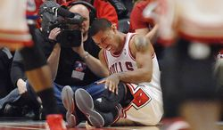 Chicago Bulls point guard Derrick Rose reacts after injuring his leg in the fourth quarter of Game 1 in the first round of the NBA basketball playoffs against the Philadelphia 76ers Saturday, April 28, 2012, in Chicago. The Bulls won 103-91. (AP Photo/Daily Herald, John Starks)