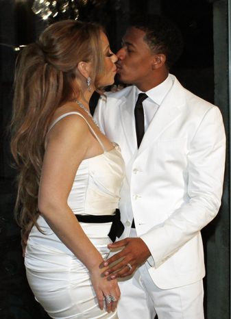 U.S singer Mariah Carey, left, kisses her husband Nick Cannon as they pose in Paris, for the renewal of their wedding vows, Friday, April 27, 2012. (AP Photo/Thibault Camus)