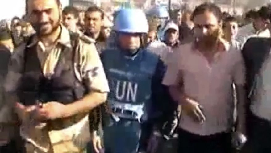 This image made from amateur video released by Shaam News Network and accessed Friday, April 27, 2012, purports to show the head of the U.N. observer team, Col. Ahmed Himmiche, center, walking in Daraa, Syria. The Associated Press cannot independently verify the content, date, location or authenticity of this material. (AP Photo/Shaam News Network via AP video)
