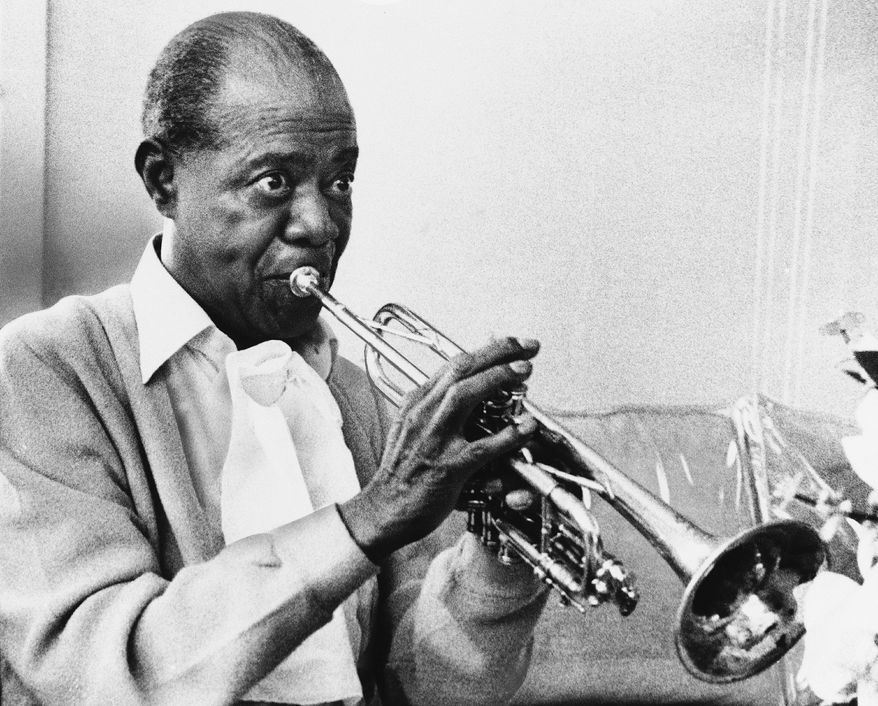 Louis Armstrong died July 6, 1971, just days after this photo of the trumpet master practicing at home in New York was taken. The jazz great broke racial barriers with his broad appeal. (Associated Press)