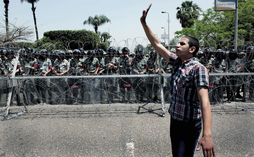 An Egyptian protester directs his fellow protesters away from the army security barrier blocking the road leading to the Ministry of Defense, in Cairo, Egypt Sunday, April 29, 2012. Assailants attacked demonstrators gathered outside the Defense Ministry in Egypt's capital to call for an end to military rule with rocks and firebombs, killing one protester and wounding scores, security officials said on Sunday. (AP Photo/Nasser Nasser)