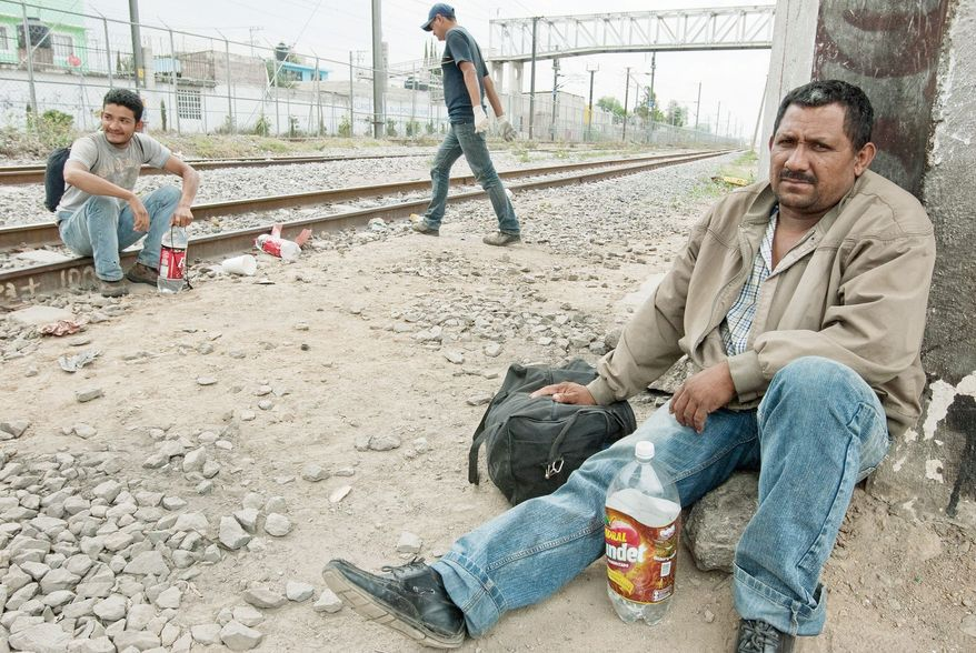 Men from Honduras migrating through Mexico on their way to the United States, wait for a northbound train. When one comes, they will run with the train until they can grab onto something and swing up onto one of the moving railcars. The men face dangers more perilous than hopping onto a moving train; abductions of more than 11,300 migrants, mostly likely by Mexico's violent drug gangs, were reported in a six-month period in 2010. (Keith Dannemiller/Special to The Washington Times)