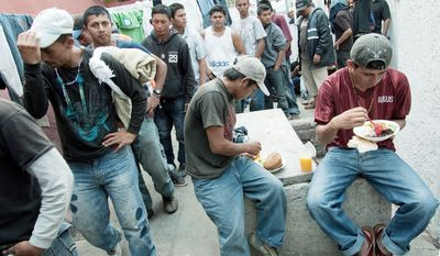 Migrants from Central America wait for a free meal of rice, beans and carrots at the San Juan Diego shelter in Tultitlan, Mexico, one stop on a journey that they hope will end with an illegal crossing into the U.S. Before that, they face a gantlet of life-or-death risks, including extortion, kidnapping, rape and killing by crooked police and criminal gangs. (Keith Dannemiller/Special to The Washington Times)