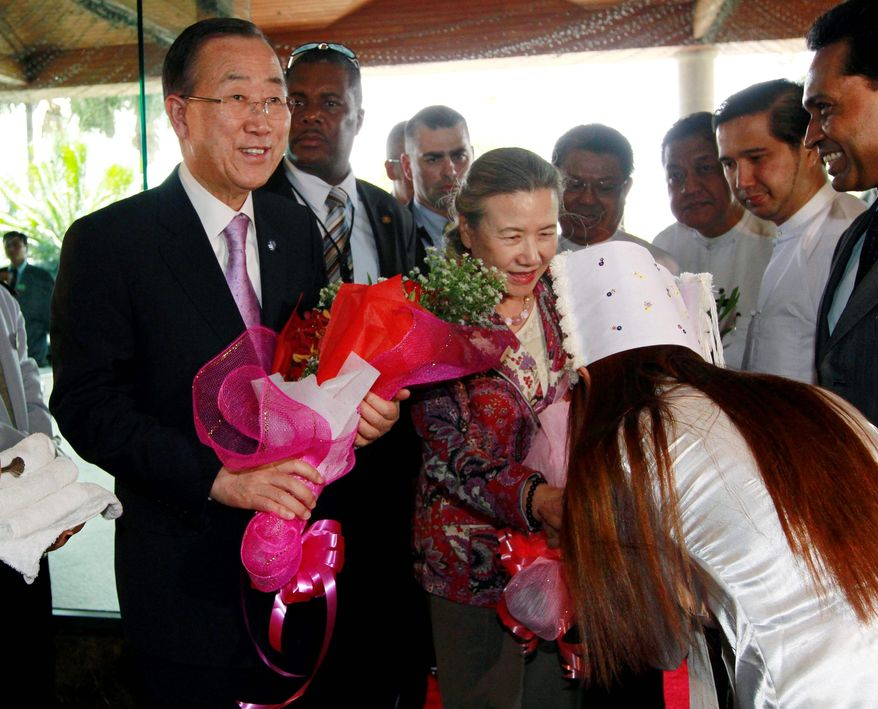 U.N. Secretary-General Ban Ki-moon (left) and his wife, Yoo Soon-taek (center), receive flowers upon their arrival in Yangon, Myanmar, on Sunday. Mr. Ban will see how the world body can help promote the country's steps toward democratic reform. He will meet President Thein Sein during the three-day visit. (Associated Press)