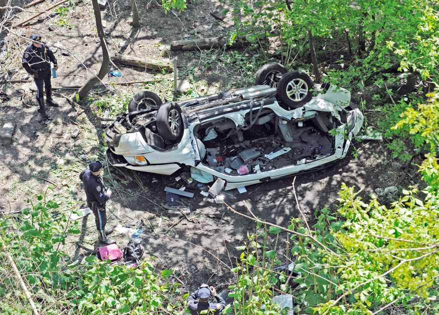 Police examine the destroyed van that plunged over the Bronx River Parkway on Sunday in New York. Authorities say the out-of-control van plunged off a roadway near the Bronx Zoo, killing seven people, including three children. (Associated Press)