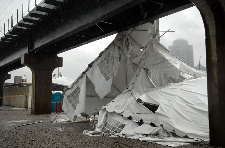 A party tent from Kilroy's Sports Bar in St. Louis rests against a railroad trestle near the bar after storm winds blew through the area near Busch Stadium on Saturday, April 28, 2012. One person died and more than a dozen were taken to a hospital with injuries in the incident. (AP Photo/Sid Hastings)