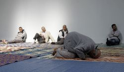 **FILE** French Muslims attend a mass prayer Sept.16, 2011, at a prayer hall in a unused former fire station in Paris. (Associated Press)