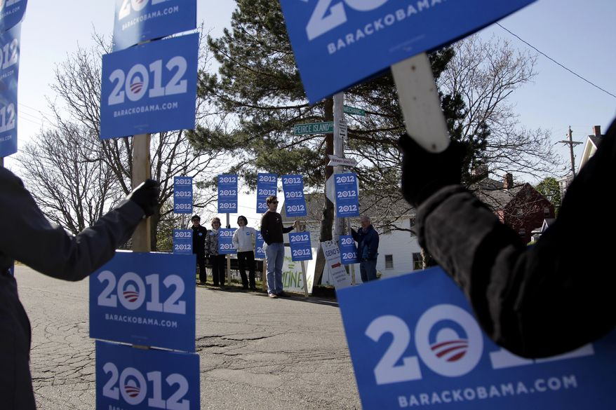 Supporters of President Obama hold signs April 30, 2012, near a campaign stop for Republican presidential candidate and former Massachusetts Gov. Mitt Romney in Portsmouth, N.H. (Associated Press)