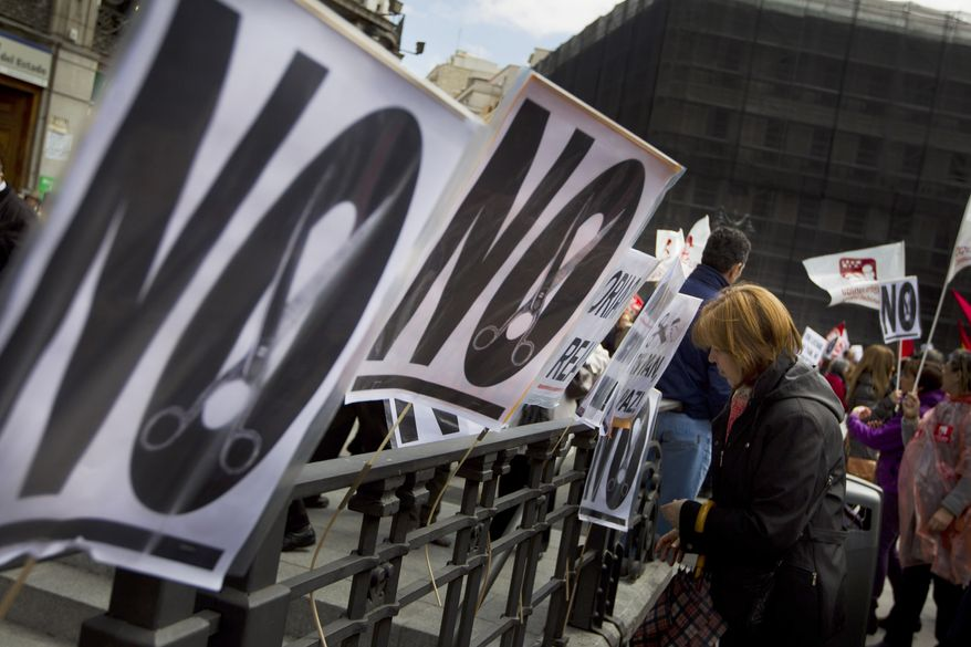 A woman leaves a banner after an April 29, 2012, demonstration against education and health care spending cuts in Madrid. (Associated Press)