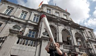 ASSOCIATED PRESS A demonstrator uses a mock marijuana cigarette as an attention-getter Tuesday during a protest rally outside the town hall in Maastricht, southern Netherlands. A policy barring foreign tourists from buying marijuana in the Netherlands went into effect in southern parts of the nation Tuesday.