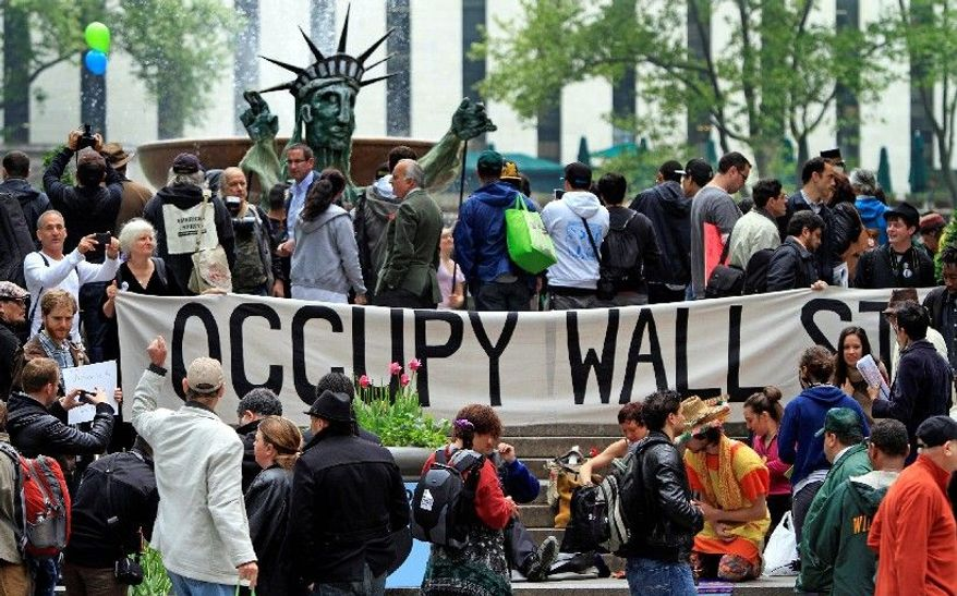 Occupy protesters unveil a banner Tuesday in New York's Bryant Park as part of worldwide May Day demonstrations. They went on to march to financial institutions, including Chase and Citibank, as the crowd grew to several hundred. (Associated Press)