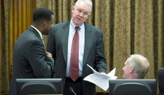 D.C. Council Chairman Kwame R. Brown (left) confers with fellow council members Tommy Wells (center) and Jack Evans. (Barbara L. Salisbury/The Washington Times)
