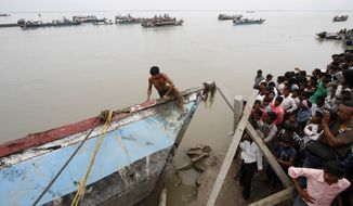 A villager climbs up to look for survivors in the wreckage of a ferry that capsized in the Brahmaputra River in Buraburi, India, about 215 miles west of the state capital, Gauhati, on Tuesday, May 1, 2012. (AP Photo/Anupam Nath)