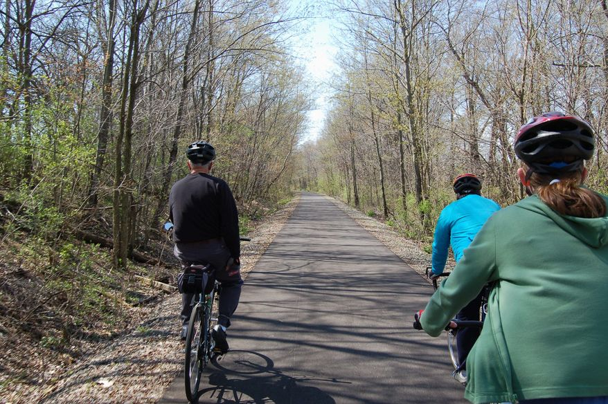"""On the Nickel Plate Trail near Bunker Hill, Ind., (from left) Rick Wagner, Karl Reusser and Esther Wagner are part of a growing number of Americans taken with biking on rail trails. """"We just started seeing how many different states we could ride a trail in,"""" he said of his family. So far, they have hit 14. """"You meet really neat people on the trails. It's just like everyone's on their best behavior."""" (Rick Wagner via Associated Press)"""