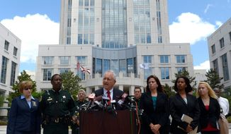 Florida State Attorney Lawson Lamar, center, announces charges against 13 people in the hazing death of Florida A&M University drum major Robert Champion during a news conference in Orlando, Fla., Wednesday, May 2, 2012. The charges were announced more than five months after Champion, 26, died aboard a chartered bus parked outside an Orlando hotel following a performance against a rival school. (AP Photo/Phelan M. Ebenhack)