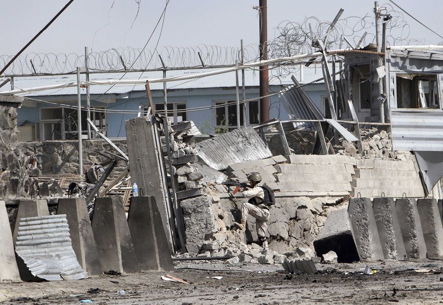 An Afghan police special force member mans the scene of a Taliban attack on a compound housing hundreds of foreigners in Kabul, Afghanistan, on Wednesday, May 2, 2012. (AP Photo/Musadeq Sadeq)