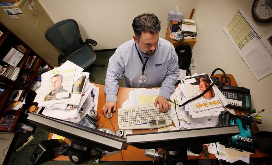 Dan Pritchett, vice president of Marketing & Business Development for Logos Bible Software, stands behind a pair of computer monitors as he works April 9, 2009, in his cluttered office in Bellingham, Wash. (Associated Press)