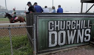 Spectators watch as horses workout at Churchill Downs on Tuesday, May 1, 2012, in Louisville, Ky. (AP Photo/Charlie Riedel)