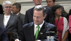 Maryland Gov. Martin O'Malley signs one of approximately 300 bills at the State House in Annapolis, Wednesday, May 2, 2012. (AP Photo/Cliff Owen)