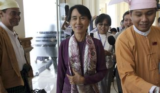 Myanmar pro-democracy leader Aung San Suu Kyi (center) arrives at parliament to attend a regular session of the body's lower house in Naypyitaw, Myanmar, on Wednesday, May 2, 2012. (AP Photo/Khin Maung Win)