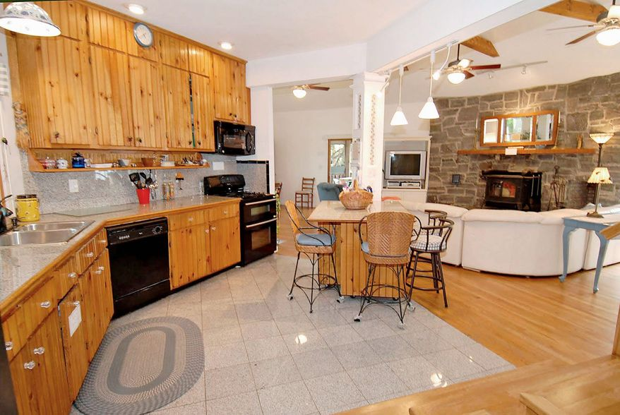 The kitchen and great room are in the home's 2003 addition. The kitchen features granite counters and ceramic tile flooring, while the great room has a stone wall and a vaulted ceiling.