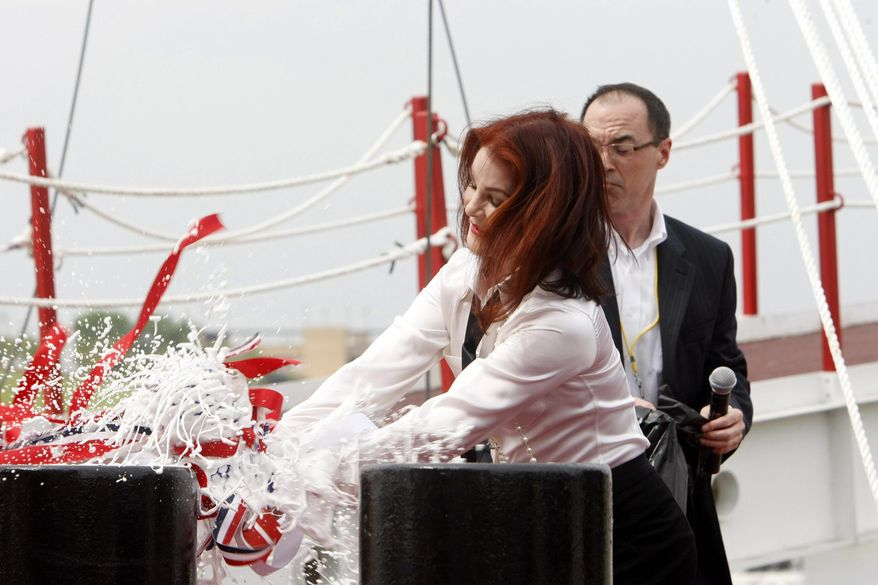 Priscilla Presley smashes a bottle of champagne on the American Queen steamboat on Friday April 27, 2012 as she rechristens the refurbished river cruise liner. She has been named as the ship's godmother. (AP photo/Karen Pulfer Focht, The Commercial Appeal)