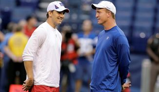 """New York Giants quarterback Eli Manning (left), with brother Peyton Manning, will host """"Saturday Night Live"""" this week after turning down a chance to do so four years ago. (Associated Press)"""
