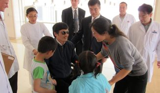 Blind dissident lawyer Chen Guangcheng meets with wife Yuan Weijing, daughter Chen Kesi and son Chen Kerui at a hospital in Beijing on Wednesday, May 2, 2012. Gary Locke, U.S. ambassador to China, is at Mr. Chen's side, as is language attache James Brown (center background). (U.S. Embassy, Beijing, via Associated Press)
