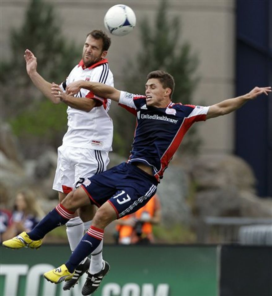 D.C. United's Daniel Woolard (21) competes for the ball against New England Revolution's Ryan Guy during the first half in Foxborough, Mass., on Saturday, April 14, 2012. (AP Photo/Elise Amendola)