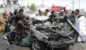 ** FILE ** Afghans push a damaged car from the scene of a militant attack by a suicide car bomber and Taliban militants disguised in burqas in Kabul, Afghanistan, on Wednesday, May 2, 2012. (AP Photo/Ahmad Jamshid)