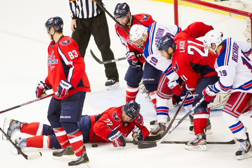 Washington Capitals defenseman Karl Alzner (27) falls on the puck in the remaining seconds in the third period as the Washington Capitals lose to the New York Rangers, 2-1, in triple overtime in playoff NHL hockey at the Verizon Center, Washington, D.C., Wednesday, May 2, 2012. (Andrew Harnik/The Washington Times)