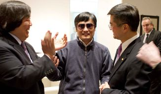 Blind lawyer Chen Guangcheng (center) holds hands with Gary Locke (right), U.S. Ambassador to China, as U.S. State Department Legal Advisor Harold Koh applauds May 2, 2012, before Chen left the U.S. embassy for a hospital in Beijing. (Associated Press/U.S. Embassy Beijing Press Office)