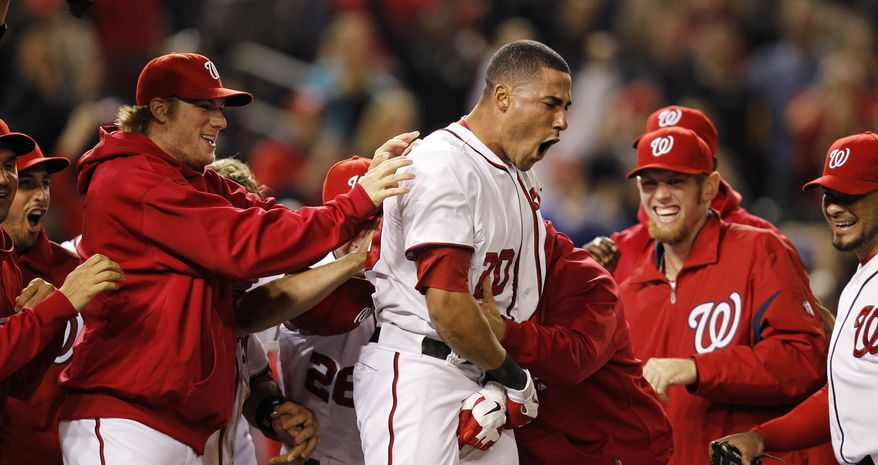 Washington Nationals' Ian Desmond celebrates with teammates after hitting a game-winning, two-run home run during the ninth inning against the Arizona Diamondbacks on Wednesday, May 2, 2012, in Washington. Bryce Harper scored on the play, and the Nationals won 5-4. (AP Photo/Haraz N. Ghanbari)