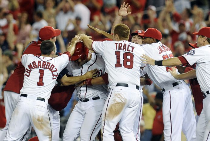 Washington Nationals' Wilson Ramos, center, is mobbed by teammates after hitting the game-winning hit scoring Steve Lombardozzi in the 11th inning to defeat the Philadelphia Phillies 4-3 during their baseball game at Nationals Park, Friday, May 4, 2012, in Washington. (AP Photo/Richard Lipski)