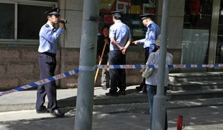 Chinese police officers question a woman and another videotape a woman protester who claims she wants to see blind lawyer Chen Guangcheng outside the hospital where Chen is recuperating in Beijing, China, Saturday, May 5, 2012. (AP Photo/Ng Han Guan)