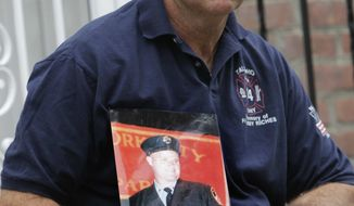 Retired firefighter Jim Riches poses for a picture with a photography of his son near his home in New York, Thursday, May 3, 2012. Riches, whose son was killed during the 2001 terrorist attacks on the World Trade center, will be among those to watch the arraignment of Khalid Sheikh Mohammed. (AP Photo/Seth Wenig)