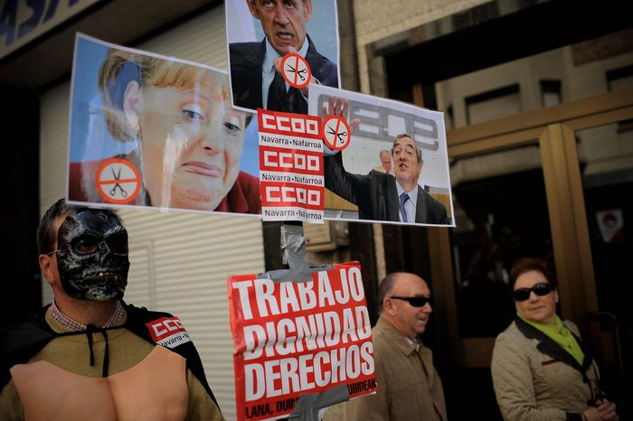 A demonstrator holds up a portrait to make fun of German Chancellor Angela Merkel, now-defeated French President Nicolas Sarkozy (center) and Spanish Employers Organization President Juan Rosell during a May Day protest Tuesday in Pamplona against the Spanish government's tough new labor reforms and cutbacks. (Associated Press)