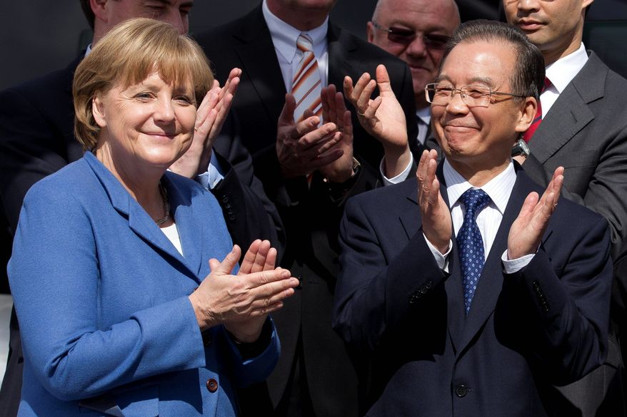 German Chancellor Angela Merkel and Chinese Prime Minister Wen Jiabao acknowledge a welcome during an April visit to the Volkswagen headquarters in Wolfsburg, Germany. The automaker will build a factory in China's far west. (Associated Press)
