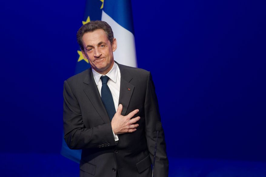 Outgoing French President Nicolas Sarkozy leaves after addressing supporters at his Union for a Popular Movement party headquarters after conceding defeat Sunday to Socialist Francois Hollande. (Associated Press)