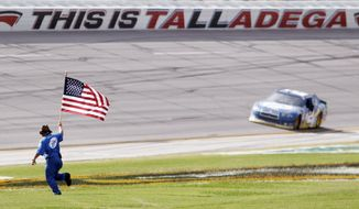 A pit crew member carries the American flag to Brad Keselowski after he won the Aaron's 499 at Talladega Superspeedway, his second Sprint Cup win of the season. (Associated Press)