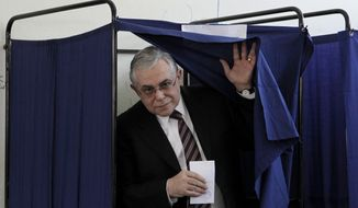 Greek Prime Minister Lucas Papademos leaves a voting booth to cast his ballot at at a voting center in Athens on Sunday, May 6, 2012. (AP Photo/Petros Giannakouris)
