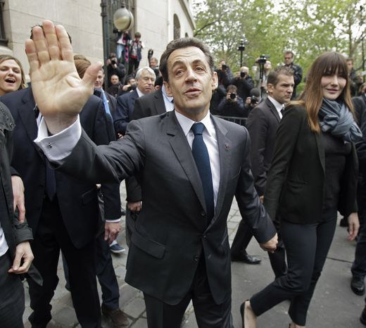 ** FILE ** French President Nicolas Sarkozy waves to well-wishers as he and his wife, Carla Bruni-Sarkozy (center right), leave after casting their votes in the second round of the French presidential elections in Paris on Sunday, May 6, 2012. (AP Photo/Michel Euler, Pool)