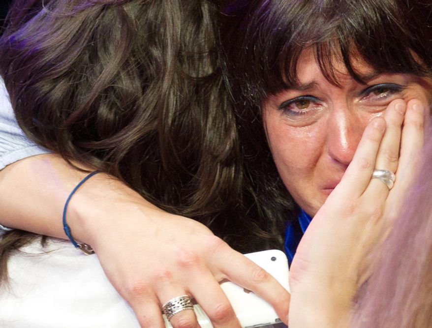 A  supporter of outgoing French President Nicolas Sarkozy's Union for a Popular Movement (UMP) covers her face as the preliminary results of the second round of the presidential elections were announced at UMP headquarters in Paris.  (AP Photo/Jacques Brinon)