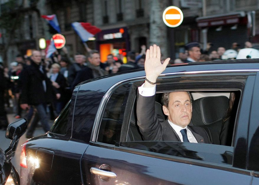Outgoing French President Nicolas Sarkozy waves from his car as he leaves after addressing supporters at his Union for a Popular Movement (UMP) party headquarters after the the preliminary results of the second round of the presidential elections were announced. (AP Photo/Thibault Camus)