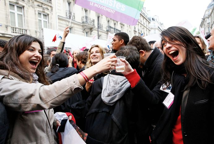 Supporters of Socialist Party candidate for the presidential election Francois Hollande celebrate with champagne after Hollande won the election.  (AP Photo/Francois Mori)