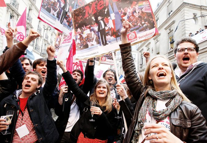 Supporters of Socialist Party candidate for the presidential election Francois Hollande celebrate with champagne after the first results of the second round of French presidential elections outside Socialist Party campaign headquarters in Paris.  (AP Photo/Francois Mori)