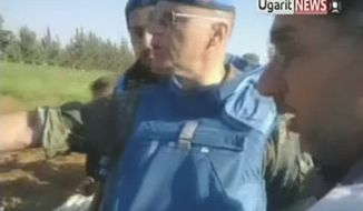 A U.N. observer (center) inspects what residents of the town of Taftanaz, Syria, tell him is a mass grave in this image made from amateur video released by Ugarit News and accessed on Saturday, May 5, 2012. (AP Photo/Ugarit News via AP video)