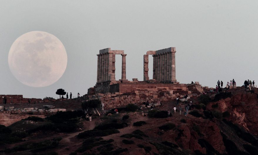 """The """"supermoon"""" appears behind the Temple of Poseidon on Cape Sounion, southeast of Athens, while tourists watch on Saturday, May 5, 2012. (AP Photo/Dimitri Messinis)"""